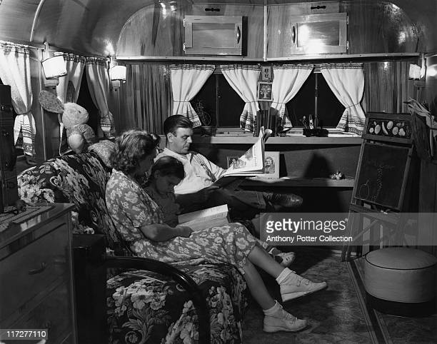 Emma D Gaw and her husband sit on a sofa with their daughter. Mr Gaw reading the newspaper with Mrs Gaw reading to their daughter in their trailer...