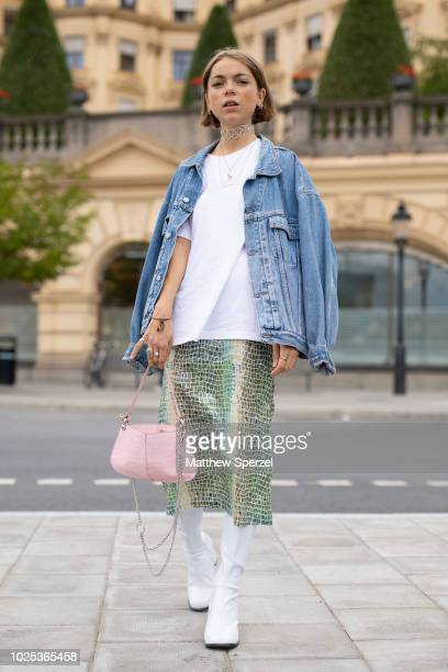 Emma Fridsell is seen on the street during Fashion Week Stockholm SS19 wearing blue denim jacket white shirt metallic green skirt white boots with...