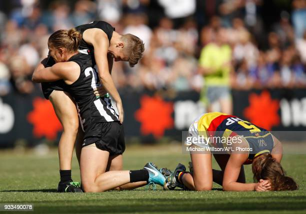 Emma Grant and Meg Hutchins of the Magpies celebrate as Jenna McCormick of the Crows slumps to the ground as the final siren sounds during the 2018...