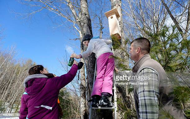 Emma Hall passes a drill up the ladder to classmate Sydney Sullivan 11 as they hang a Northern Flicker nesting box as part of the Center for Teaching...
