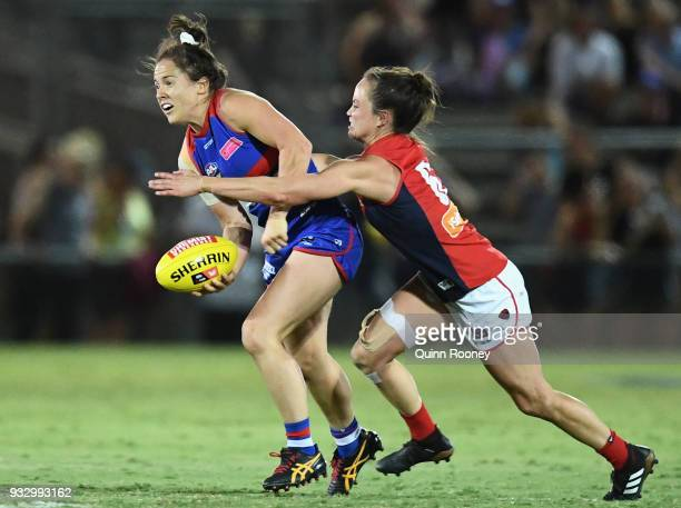 Emma Kearney of the Bulldogs handballs whilst being tackled by Daisy Pearce of the Demons during the round seven AFLW match between the Western...