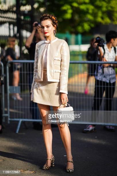 Emma Mackey wears earrings a shiny beige jacket a skirt a white bag leopard print shoes outside Miu Miu Club 2020 on June 29 2019 in Paris France