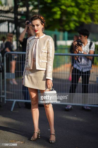 Emma Mackey wears earrings, a shiny beige jacket, a skirt, a white bag, leopard print shoes, outside Miu Miu Club 2020, on June 29, 2019 in Paris,...