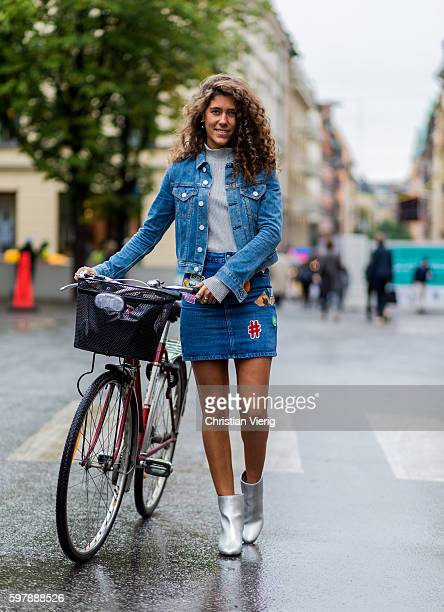 Emma Mattson with her bike wearing a light blue denim jacket and a short mini denom skrit with patches and silver boots outside Stylein during the...