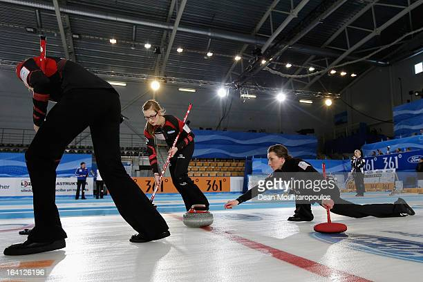 Emma Miskew of Canada throws a stone as Alison Kreviazuk and Lisa Weagle sweep in the match between Canada and Germany on Day 5 of the Titlis Glacier...