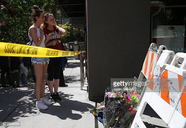 Emma Nicholson and Gemma Parsons stand next to a memorial of flowers at the scene of a balcony collapse at an apartment building near UC Berkeley on...
