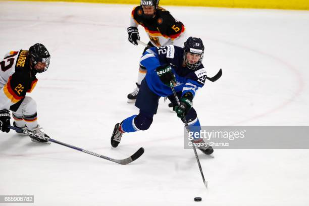 Emma Nuutinen of Finland passes around the stick of Marie Delarbre of Germany during the first period in the bronze medal game at the 2017 IIHF...
