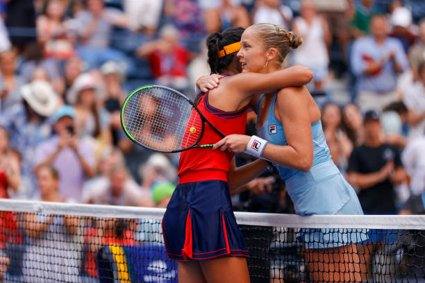 Emma Raducanu of the United Kingdom meets at the net after defeating Shelby Rogers of the United States during her Women's Singles round of 16 match...