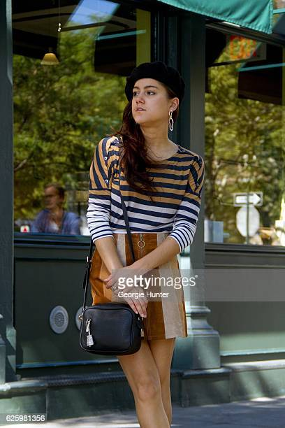 Emma Sousa wearing wide neck blue white and tan horizontal striped long sleeved cotton top by Old Navy with shoulder buttons tan brown and cream...