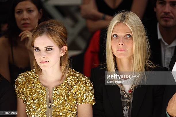 Emma Watson and Gwyneth Paltrow dressed in Burberry watch the Burberry Prorsum Spring/Summer 2010 Show at Rootstein Hopkins Parade Ground during...