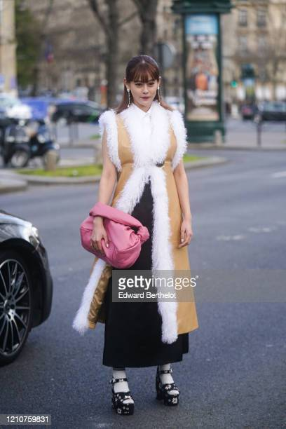 Emma wears long bejeweled earrings a creamcolor long sleeveless coat with white fluffy parts a pink puff bag floral print shoes white socks outside...