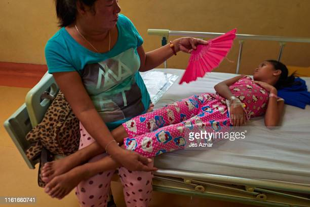 Emmalyn Guadamor attends to her daughter who has dengue Kricia Mae at the San Lazaro Hospital on August 14 2019 in Manila Philippines The Philippines...