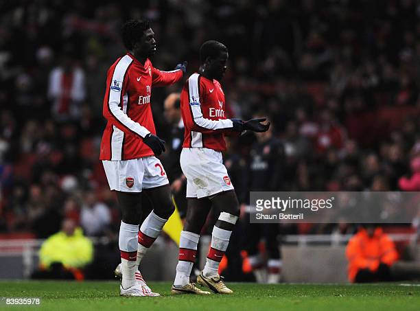 Emmanuel Adebayor of Arsenal consoles Emmanuel Eboue as he is substituted during the Barclays Premier League match between Arsenal and Wigan Athletic...