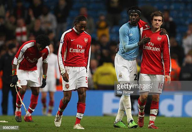 Emmanuel Adebayor of Man City consoles Aaron Ramsey at the end of the Carling Cup quarter final match between Manchester City and Arsenal at City of...