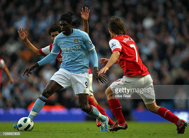 Emmanuel Adebayor of Manchester City takes the ball past Tomas Rosicky of Arsenal during the Barclays Premier League match between Manchester City...