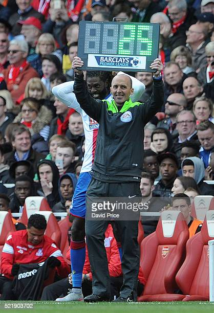 Emmanuel Adebayor of Palace and 4th official Mike Dean prepare for Adebayor to come on during the Barclays Premier League match between Arsenal and...