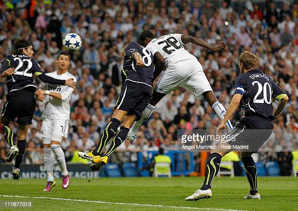 Emmanuel Adebayor of Real Madrid heads the ball against Jermaine Jenas of Tottenham to score his side opening goal during the UEFA Champions League...