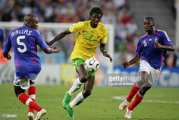 Emmanuel Adebayor of Togo runs inbetween William Gallas and Claude Makelele of France during the FIFA World Cup Germany 2006 Group G match between...
