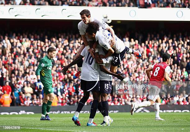 Emmanuel Adebayor of Tottenham Hotspur is mobbed by team mates after scoring his penalty during the Barclays Premier League match between Arsenal and...
