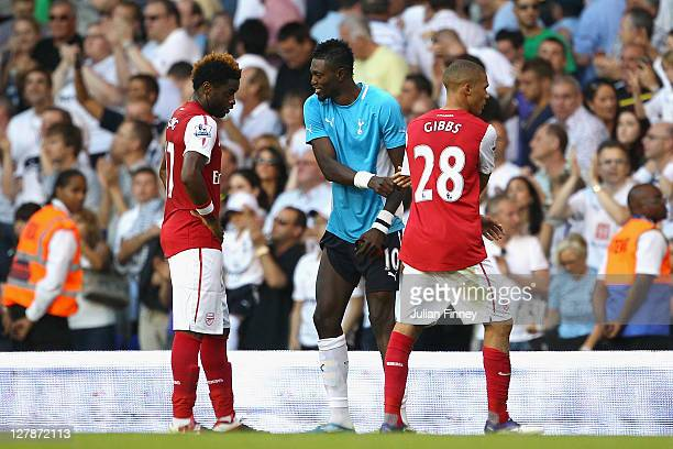 Emmanuel Adebayor of Tottenham Hotspur shakes the hands of his former team mates Alex Song and Kieran Gibbs of Arsenal during the Barclays Premier...