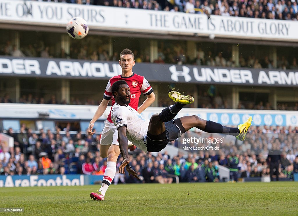 Emmanuel Adebayor of Tottenham Hotspur with an acrobatic effort watched by Laurent Koscielny of Arsenal during the Premier League match between Tottenham Hotspur and Arsenal at White Hart Lane on March 16, 2014 in London, England.