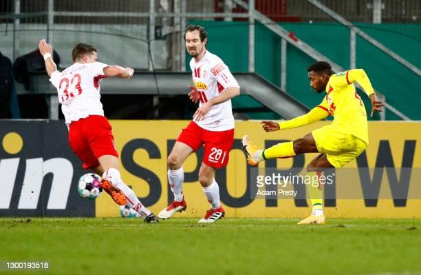 Emmanuel Bonaventure of 1. FC Koeln scores their side's first goal whilst under pressure from Jan Elvedi and Sebastian Nachreiner of Jahn Regensburg...