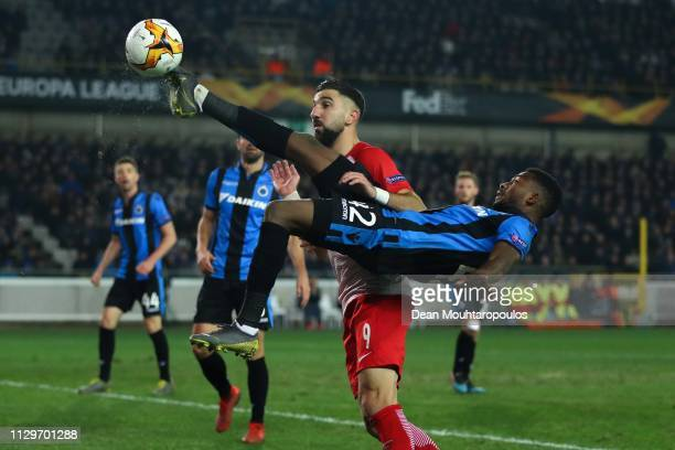 Emmanuel Bonaventure of Club Brugge clears the ball under a challenge Munas Dabbur of FC Salzburg during the UEFA Europa League Round of 32 First Leg...