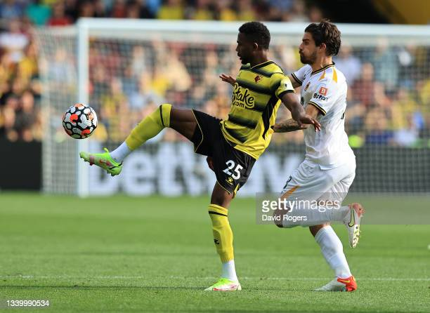 Emmanuel Dennis of Watford controls the ball watched by Ruben Neves during the Premier League match between Watford and Wolverhampton Wanderers at...