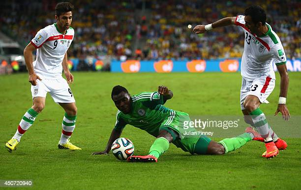 Emmanuel Emenike of Nigeria competes for the ball with Alireza Jahan Bakhsh and Mehrdad Pooladi of Iran during the 2014 FIFA World Cup Brazil Group F...