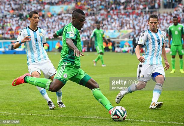 Emmanuel Emenike of Nigeria controls the ball against Angel di Maria and Fernando Gago of Argentina during the 2014 FIFA World Cup Brazil Group F...