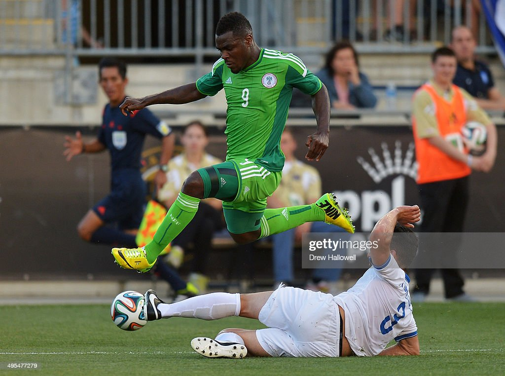 Emmanuel Emenike #9 of Nigeria jumps over Giorgos Tzavellas #3 of Greece during an international friendly match at PPL Park on June 3, 2014 in Chester, Pennsylvania.