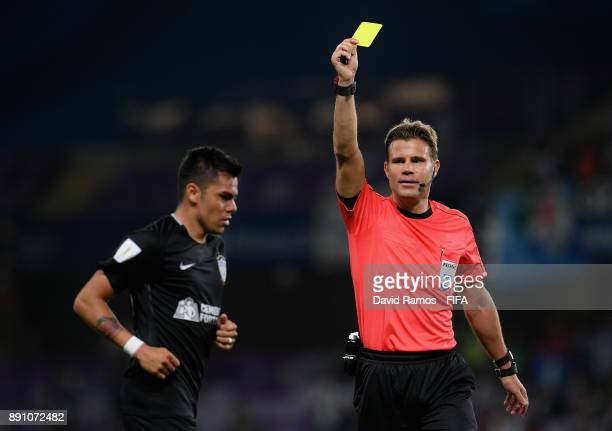 Emmanuel Garcia of CF Pachuca is booked by referee Felix Brych during the FIFA Club World Cup UAE 2017 semifinal match between Gremio FBPA and CF...