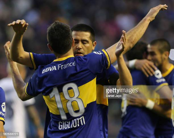Emmanuel Gigliotti, of Boca Juniors, celebrates with teammate Juan Roman Riquelme after scoring during a match between Boca Juniors and Quilmes as...