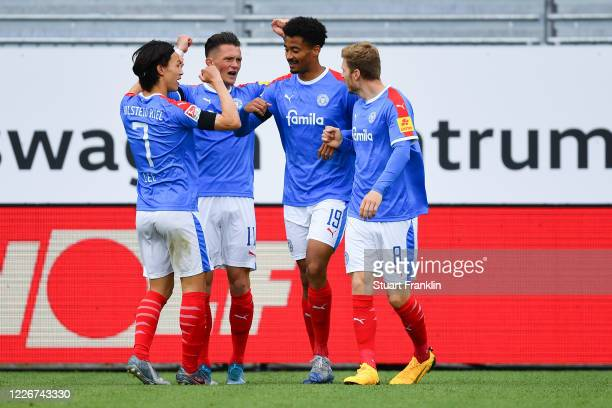 Emmanuel Iyoha of Kiel celebrates his team's first goal with team mates Alexander Muehling Fabian Reese and Jaesung Lee during the Second Bundesliga...