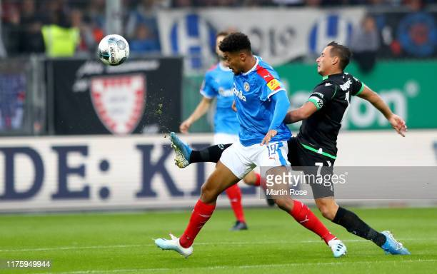 Emmanuel Iyoha of Kiel challenges Edgar Prib of Hannover during the Second Bundesliga match between Holstein Kiel and Hannover 96 at HolsteinStadion...