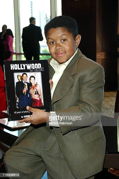 Emmanuel Lewis holding a Book that shows Photographs taken by Photographer Bill Jones