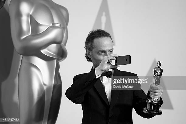 Emmanuel Lubezki winner of the Best Cinematography Award for 'Birdman' photographs his Oscar in the press photo room at the 87th Annual Academy...