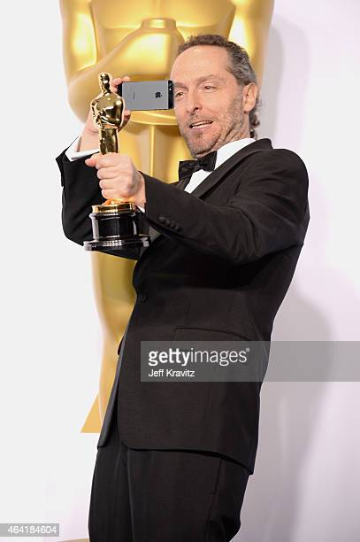 """Emmanuel Lubezki, with the award for best cinematography for """"Birdman"""", poses in the press room during the 87th Annual Academy Awards at Loews..."""