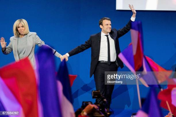 Emmanuel Macron France's independent presidential candidate and his wife Brigitte Trogneux wave as they arrive to deliver a speech after the first...