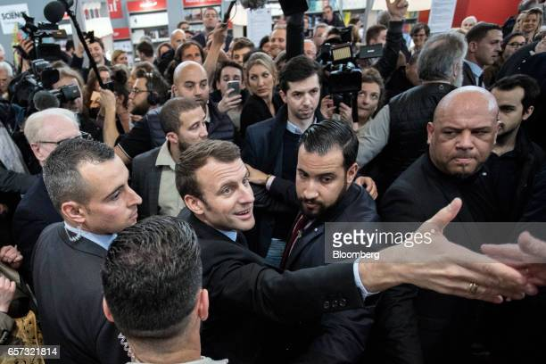 Emmanuel Macron France's independent presidential candidate centerwith Alexandre Benalla shakes hands with an attendee as he visits the Salon du...
