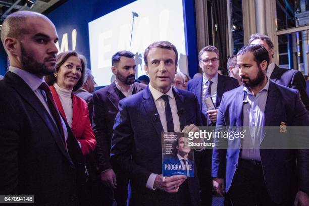 Emmanuel Macron France's independent presidential candidate poses for photographers with his presidential manifesto after presenting his election...