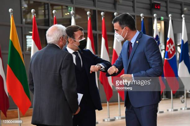 Emmanuel Macron, France's president, center, greets Pedro Sanchez, Spain's prime minister, right, with an 'elbow bump' beside Josep Borrell, vice...