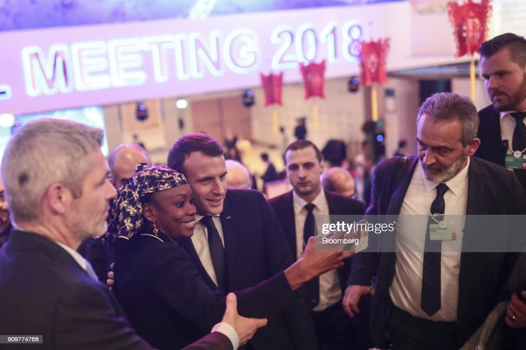 Emmanuel Macron, France's president, center, poses for a selfie photograph with an attendee between sessions on day two of the World Economic Forum (WEF) in Davos, Switzerland, on Wednesday, Jan. 24, 2018. World leaders, influential executives, bankers and policy makers attend the 48th annual meeting of the World Economic Forum in Davos from Jan. 23 - 26. Photographer: Simon Dawson/Bloomberg via Getty Images
