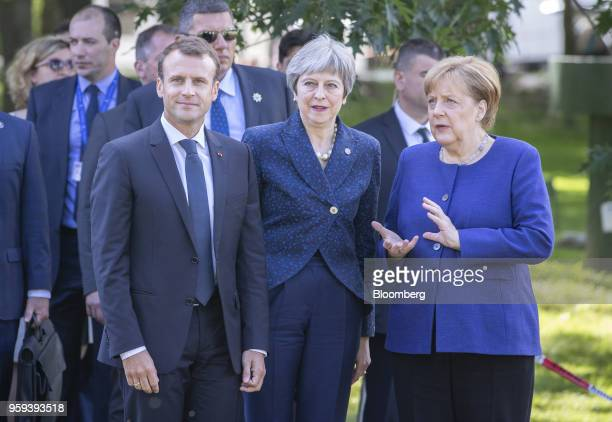 Emmanuel Macron France's president left and Theresa May UK prime minister center look on as Angela Merkel Germany's chancellor talks during a walk in...