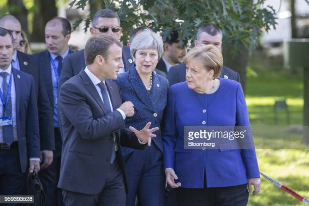 Emmanuel Macron France's president left Theresa May UK prime minister center and Angela Merkel Germany's chancellor walk in the gardens of the...