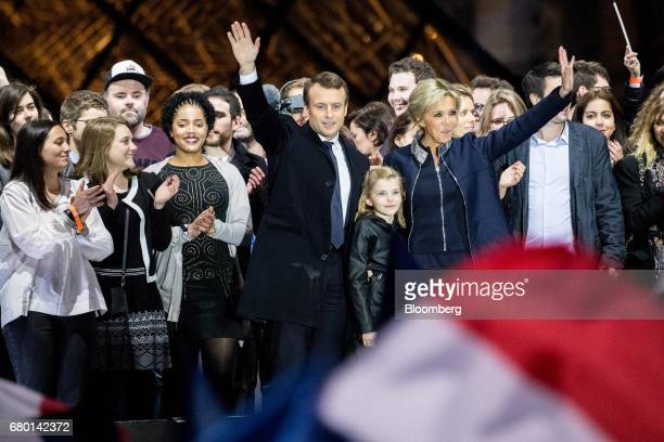 Emmanuel Macron French presidential candidate center left waves while standing with his wife Brigitte Trogneux in front of the Pyramid at the Louvre...