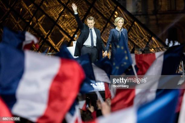 Emmanuel Macron French presidential candidate left waves while standing with his wife Brigitte Trogneux in front of the Pyramid at the Louvre Museum...