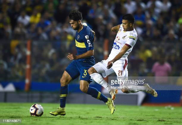 Emmanuel Mas of Boca Juniors fights for the ball with Juan Arboleda of Deportes Tolima during a group G match between Boca Juniors and Deportes...