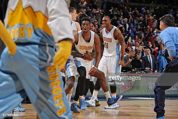 Emmanuel Mudiay of the Denver Nuggets celebrates with his teammates after hitting the game winning three point shot against the Philadelphia 76ers on...