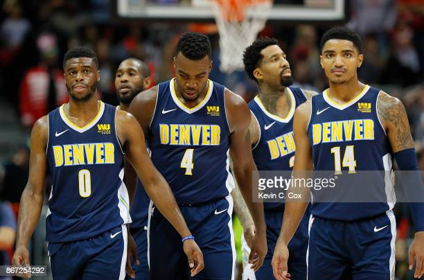 Emmanuel Mudiay Paul Millsap and Gary Harris of the Denver Nuggets walk off the court during a timeout against the Atlanta Hawks at Philips Arena on...